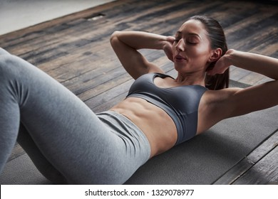 Makes inhale. Top view of girl with slender body works on the abs when lying on the floor.