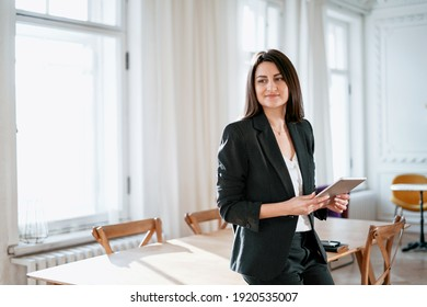 Makes an order in the online store lunch food. In a modern office. The economist is a brunette woman. The manager works on a tablet computer. Business stylish black suit.