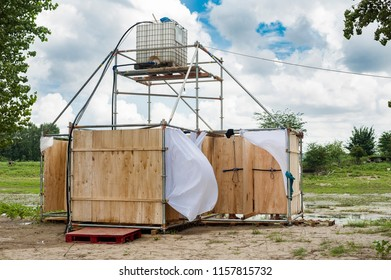 Makeshift showers/Abstract image of a improvised showers with a water tank on top on a danube island with the wind blowing out the cabin curtains.