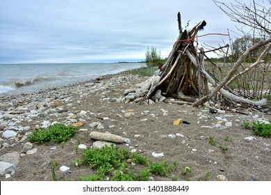 A make-shift Tee Pee shaped shelter built from driftwood and other materials found along the shore of Lake Michigan in Kenosha Wisconsin  with crashing waves and stormy skies in the background.