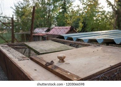 Make-shift wooden panels seen used for making various types of chicken shelters and houses in a large garden. The background shows a fence and various metal panel used to help build the shelters.