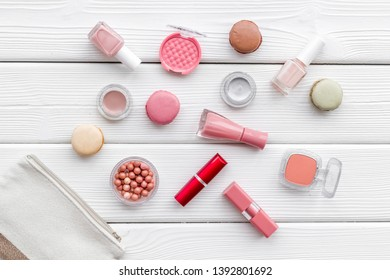 make-up accessories, fashion stylish cosmetics and macaroon on white wooden desk background top view pattern
