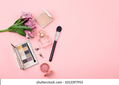 The makeup and accessories on a pink background with space for text