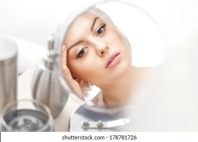 Makeup Applying. Beautiful Woman Looking at Her Face in the Miror Doing Daily Morning Makeup