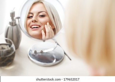 Makeup Applying. Beautiful Woman Looking at Her Face in the Miror. Daily Morning Makeup