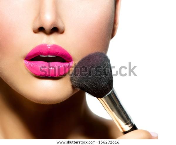 Make-up. Machen Sie die Anwendung Nahaufnahme aus. Kosmetischer Pullover zum Make-up. Perfekte Haut. violetter Lipstick. Einzeln auf weißem Hintergrund. Erschaffen