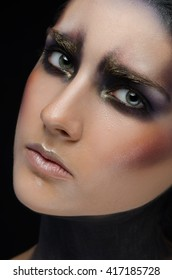 Makeup art and model theme: beautiful girl with a creative make-up black-and-purple and gold colors on a black background in the studio shot