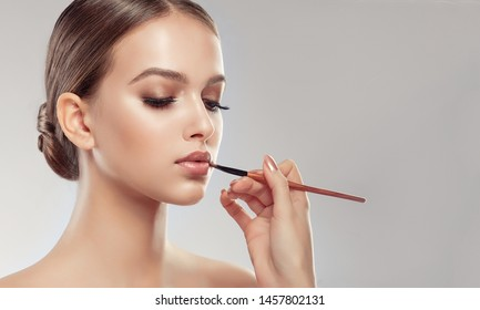 Makeup artist applies  beige gloss  lipstick  . Beautiful woman face. Hand of make-up master, painting lips of young beauty  model girl . Make up in process