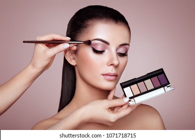 Makeup Artist applies Eye Shadow. Beautiful Woman Face. Perfect Makeup. Make-up detail. Beauty Girl with Perfect Skin. Nails and Manicure. Eye Shadow Palette
