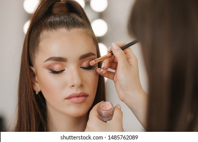 Makeup artist applies eye shadow, perfect evening makeup. Beauty redhead girl with perfect skin and freckles