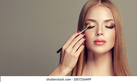 Makeup artist applies  eyeshadow  . Beautiful woman face. Hand of make-up master, painting eyes of young beauty  model girl . Make up in process