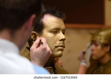 A make-up artist applies gold paint to an actor's face before a performance