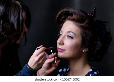 Makeup artist applies lips a red lipstick. Beautiful woman face. Perfect makeup on retro pinup or vintage pin up style