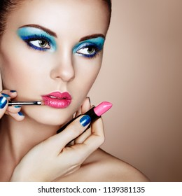 Makeup Artist Applies Lipstick. Beautiful Woman Face. Makeup detail. Beauty Model with Perfect Skin. Pink Lips and Blue Nails Manicure