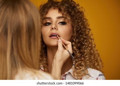 Makeup artist applies lipstick . Beautiful woman face. Hand of make-up master, painting lips of young beauty model girl . Make up in process
