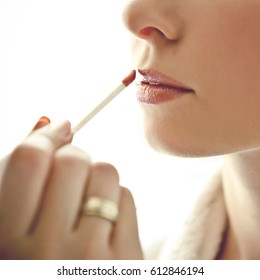 make-up artist applies lipstick to bride on white background