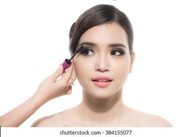 Makeup artist applies mascara. Beautiful woman face. Perfect makeup