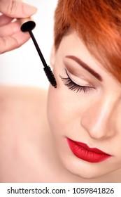 Makeup artist applies mascara brush. Beautiful young woman with short red hair. Makeup detail.