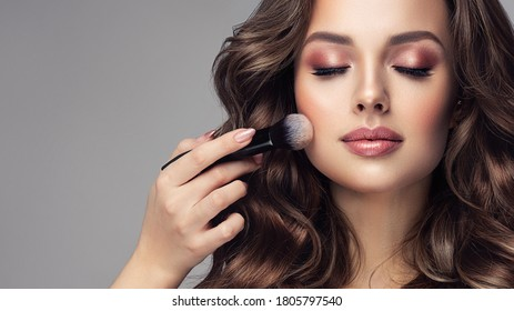 Makeup artist applies   applies powder and blush  . Beautiful woman face. Hand of make-up master puts blush on cheeks  beauty  model girl . Make up in process