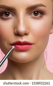 Makeup artist applies red lipstick. Beautiful female face. Hand of a make-up master painting lips of a young girl beauty model. Makeup in progress