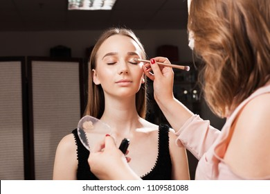 makeup artist appling a primer on an eyelid of a young beautiful model using a brush before dabbing eyeshadows. concept of professional make up training