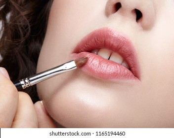 Make-up artist apply beauty makeup on the lips of a beautiful girl. Visagist with makeup brush in hand.