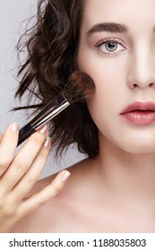 Make-up artist apply beauty makeup on the face of a beautiful girl. Visagist with makeup brush in hand.