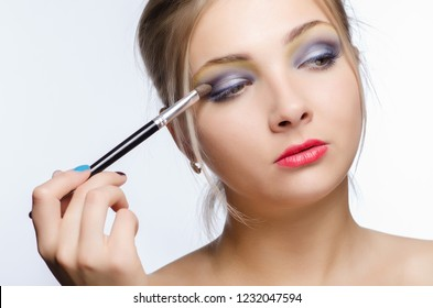 Make-up artist apply beauty makeup on the face of a beautiful girl.