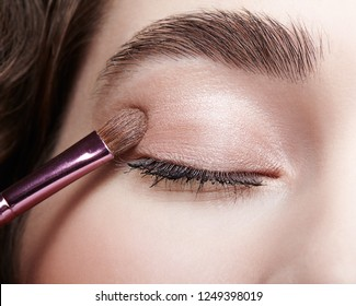 Make-up artist apply beauty makeup on the eyelids on face of a beautiful girl. Visagist with makeup brush in hand.
