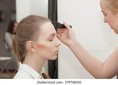 Makeup artist apply makeup bMakeup artist apply makeup beautiful young girl before the photoshoot