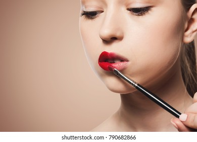 Make-up artist apply lipstick with brush. Closeup of female model face with fashion glossy red lips makeup, beauty concept, copy space