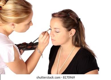 Makeup artist applying base to models face