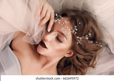 Make-up artist applying bright base color eyeshadow on model's eye and holding a shell with eyeshadow on background, close up,wedding accessory ,amazing girl.Beauty Eyelash extensions, false eyelashes