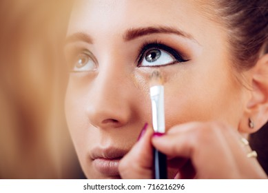 Makeup artist applying concealer on a beautiful young woman's face. Close up.