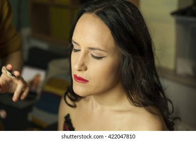 Make-up artist applying cosmetics to a model in a set, shoot in studio.