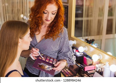 The makeup artist applying the eye shadow to the charming young woman indoors