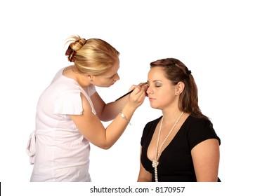 Makeup artist applying eye shadow to model's face