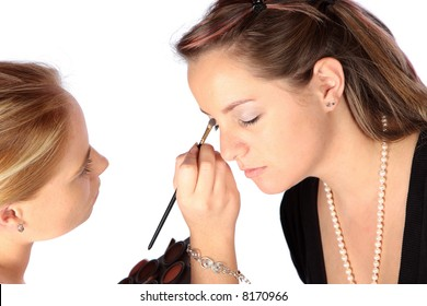 Makeup artist applying eye shadow to a young model