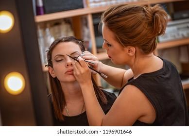 Make-up artist applying the eyeliner to model. Close up.