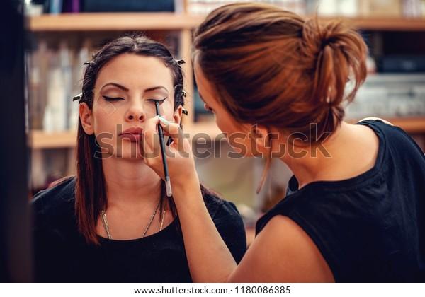 Make-up artist applying the eyeliner to model.