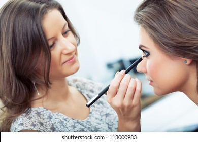 Make-up artist applying eyeliner on model's lower lid, selective focus on model, close up