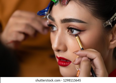 Makeup artist applying eyeliner to  waterline by using eyeliner brush for making perfect makeup before charming beautiful model do her work. Attractive beautiful girl has perfect face, beautiful eyes