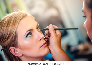 Make-up artist applying the eyeshadow to model. Close-up.