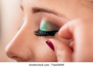 Makeup artist applying the false eyelashes to model. Close up.