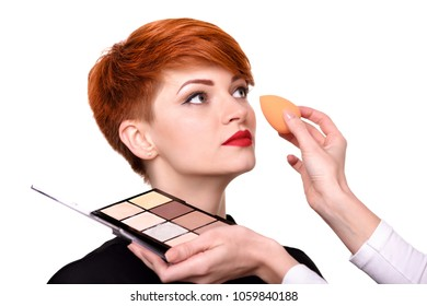 Makeup artist applying foundation on young woman's face using sponge. Beautiful young woman with short red hair. Makeup detail.