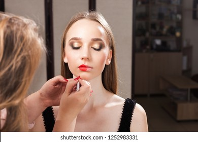 makeup artist applying lipstick on a young beautiful client. makeup is halved on lips of the girl. concept of professional make up training