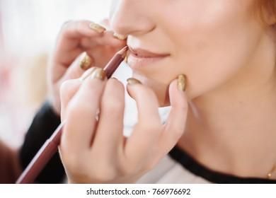 make-up artist applying lipstick on female lips. The bride morning