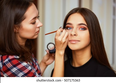 Make-up artist applying liquid eyeliner with brush, close up.