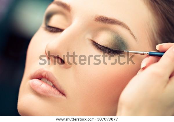 Make-up artist applying liquid eyeliner on model's eyes, close up