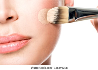 Makeup artist applying liquid tonal foundation  on the face of the woman. Closeup photo of cheek